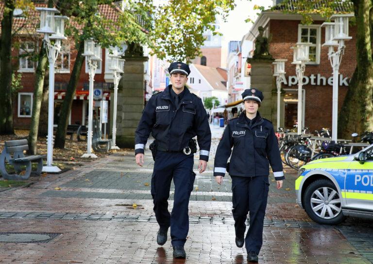 Eine Polizistin und ein Polizist zu Fuß auf Streife in einer Innenstadt