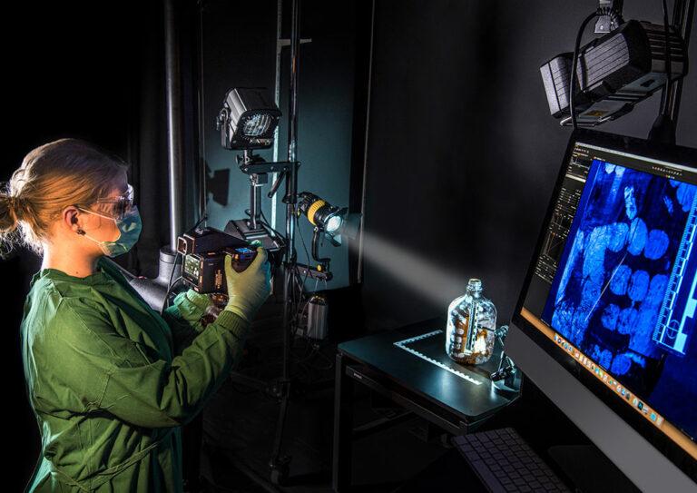 Kriminaltechnickerin untersucht Fingerabdrücke auf einer Flasche mit moderster Technik