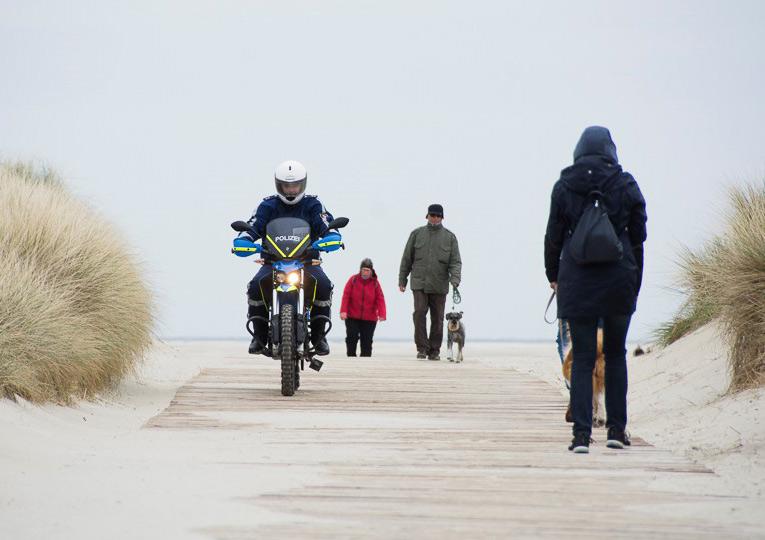 Ein Polizist auf einem Polizei Motorrad in den Dünen