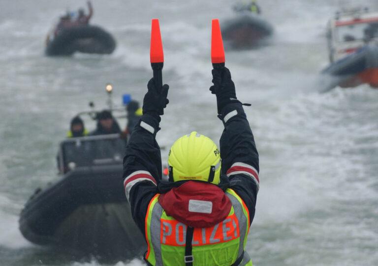 Ein Lotse der Wasserschutzpolizei weist mehreren Booten den Weg