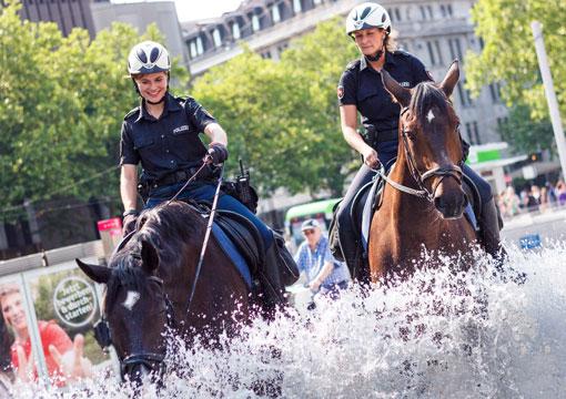 Zwei Polizistinnen auf Pferden am Brunnen in der Innenstadt